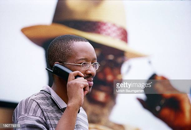 Coloured man is making a phonecall with a mobile phone in front of a poster with advertisment for Vodacom