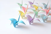 Coloured origami birds flying to the light