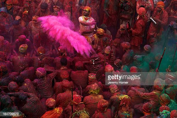 Coloured powders are released over devotees gathered at the Krishna Temple of Shriji during Lathmar Holi Men from Barsana raid the town whilst being...
