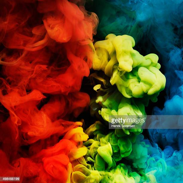 coloured smoke mixing in dark room