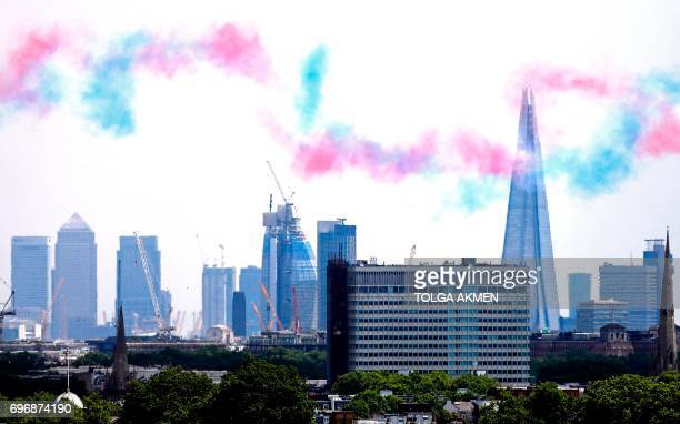 TOPSHOT Coloured smoke trails hang in the air backdropped by The Shard skyscraper and One Canada Sqaure in the Canary Wharf district of east London...
