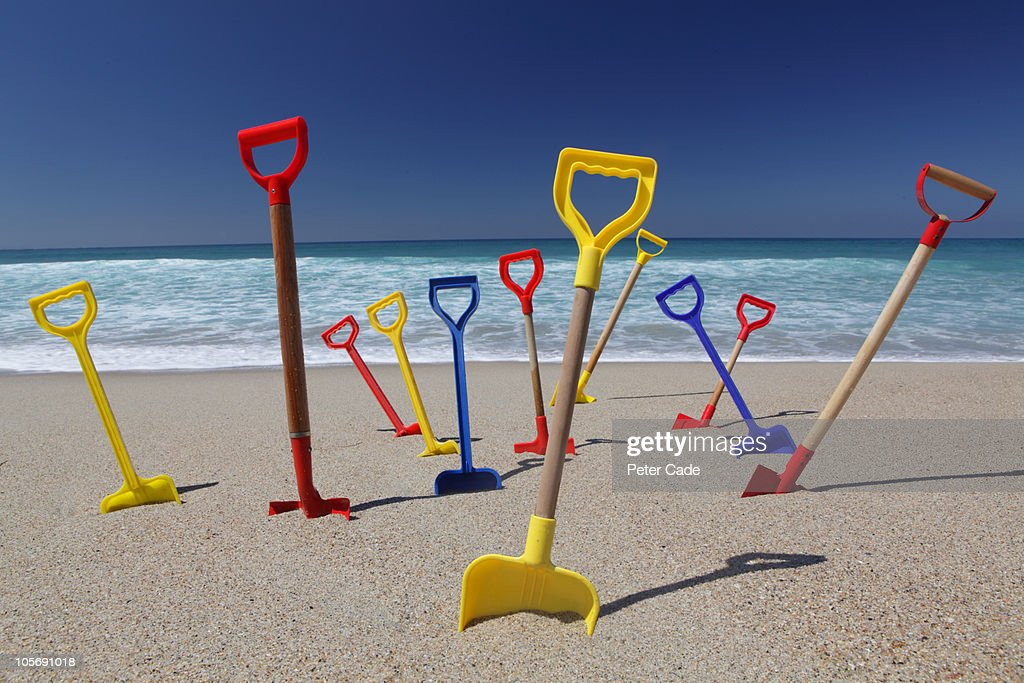 coloured spades stuck in sand on beach : Stock Photo