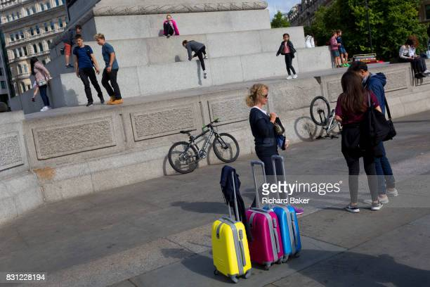 Coloured suitcases as young tourists play on the plinth of Nelson's Column in Trafalgar Square on 10th August 2017 in London England