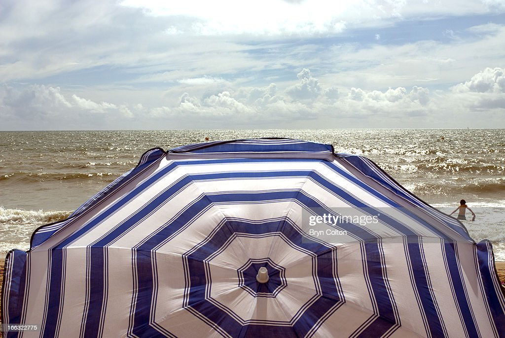A coloured sun parasol shields a sunbather as they sit on the beach and look out over the Bay of Biscay, from coast near Saint-Jean-de-Monts, Vendee, France, on Saturday, August 19, 2006.