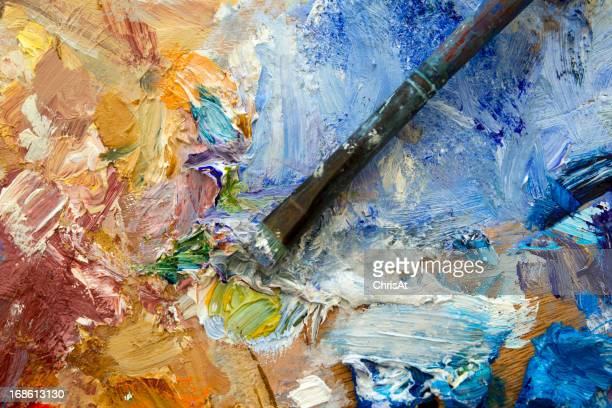 Colourful artists oil paint palette and brush close up