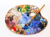 Colourful artists oil paint palette and brushes close up on plain background