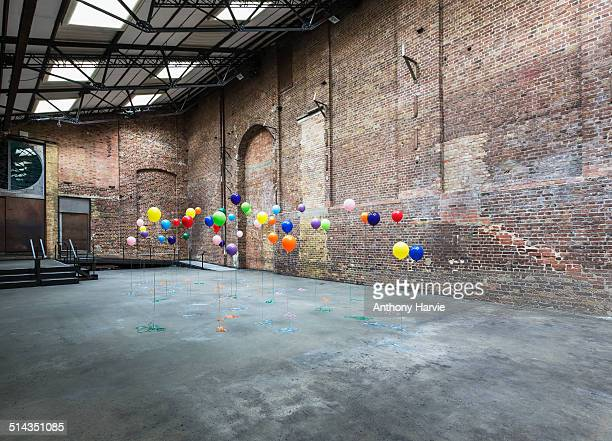 Colourful balloons in empty warehouse