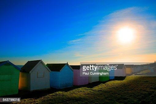 Colourful beach huts bask in the setting sun