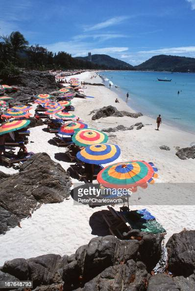 Colourful beach umbrellas line Patong beach one of the most popular tourist areas on this resort island