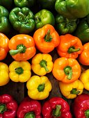 Looking down from above onto red, green, yellow and orange bell peppers on a market stall