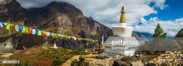 Colourful Buddhist prayer flags white stupa Sherpa village Himalayas Nepal