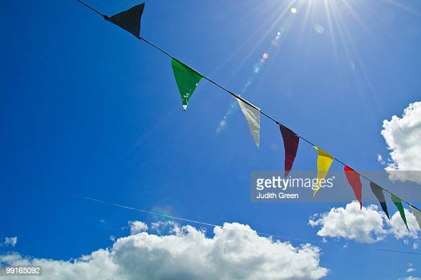 Colourful bunting against a blue sky with sunflare