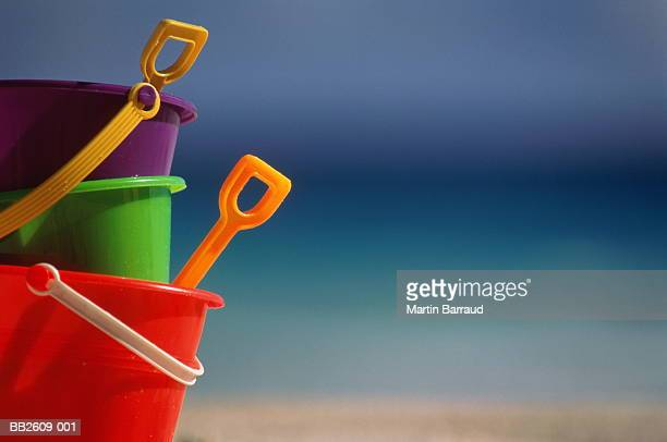 Colourful child's plastic buckets and spades on beach