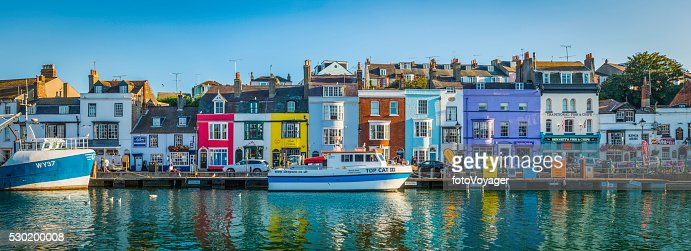 カラフルなコテージには、のどかな海辺の漁村の港の英国ドーセット