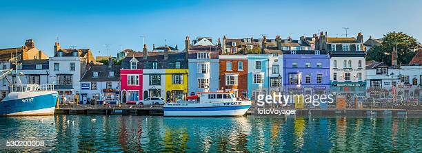 Colourful cottages in idyllic seaside fishing village harbour Dorset UK