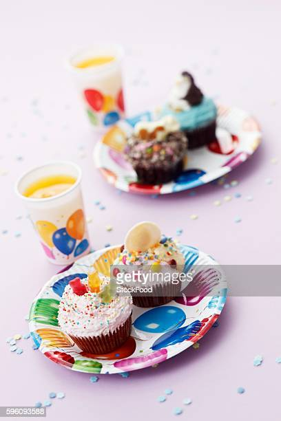 Colourful cupcakes and orange juice for a child's birthday party