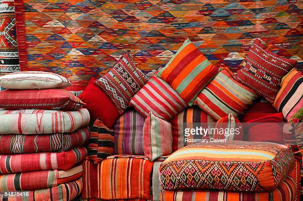 Colourful cushions and carpets in street market.