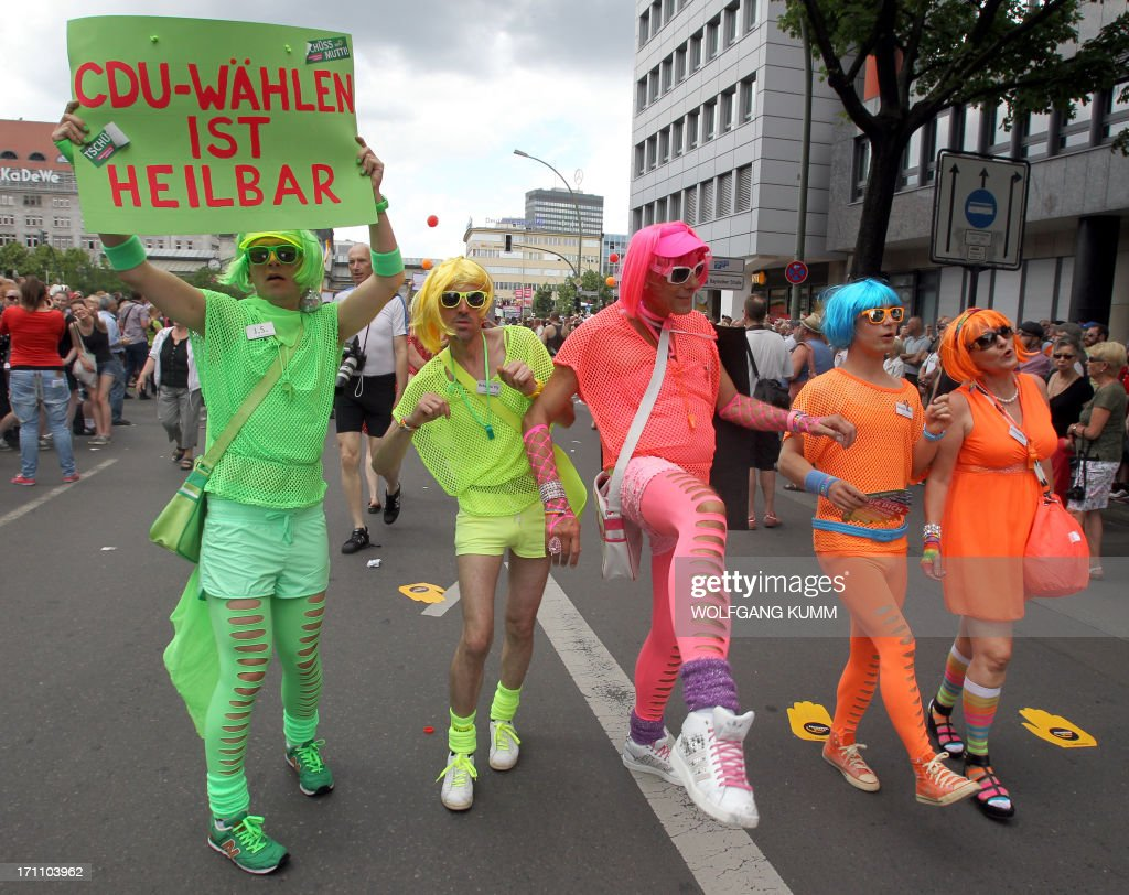 Colourful dressed participants carry a banner that reads 'Voting for the Christian Democrats (CDU) can be cured'' as they take part at the Christopher Street Day Parade (CSD) in Berlin, Germany, on June 22, 2013. Demanding equal rights for same-sex couples, tens of thousands of people began to march Saturday, June 22, 2013 in Berlin for the 35th edition of the Gay Pride high in color and political accents three-month ahead of the legislative elections. AFP PHOTO / WOLFGANG KUMM GERMANY OUT