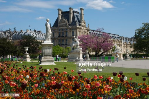 Colourful flower garden and statues in Jardin de Tuileries in front of Royal Palace.