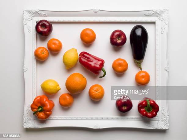Colourful fruit and vegetables displayed in a white picture frame on a white background