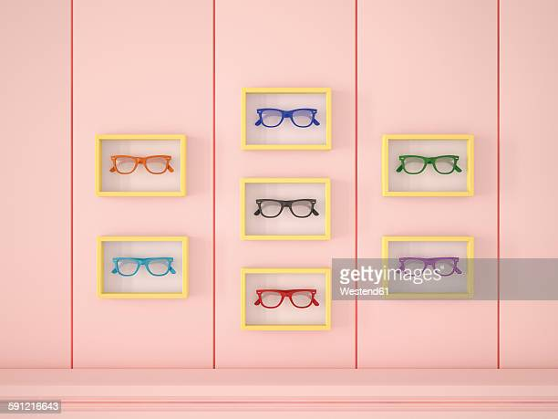 Colourful glasses in yellow frames hanging on pink wall