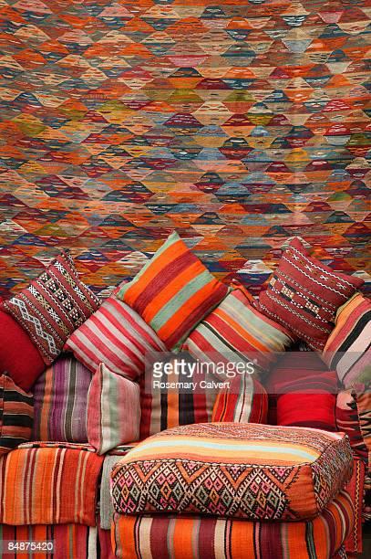 Colourful handmade cushions and carpet.