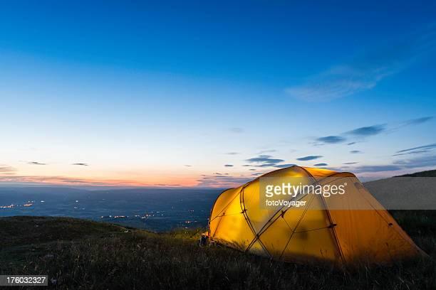 Bunte beleuchtet Zelt high auf die Berge bei Dämmerung unter blauen Himmel