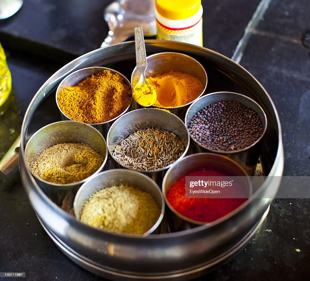 Colourful indian spices like cumin coustard seeds red chili powder garam masala and tumeric powder that are used in the kitchen of Yoga Magic Eco...