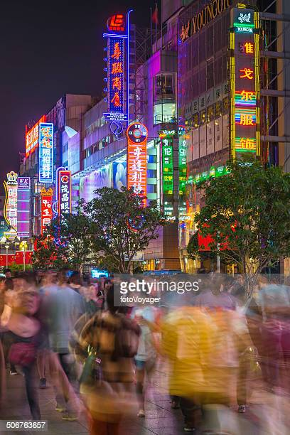 Colourful neon signs above crowds on Nanjing Road Shanghai China