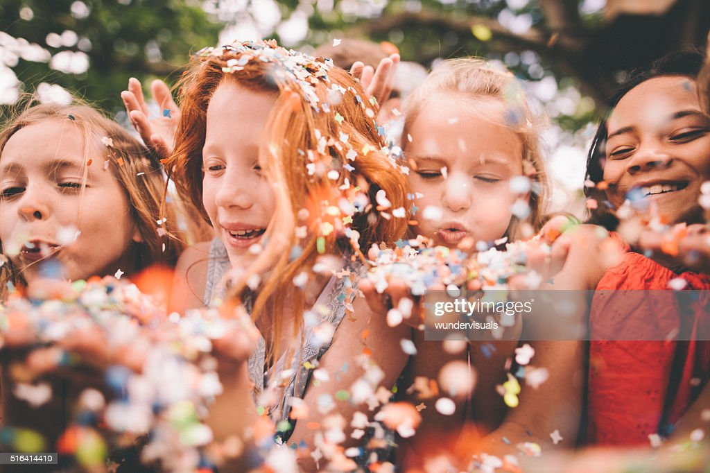 Colourful paper confetti being blown at the camera by children : Stock Photo