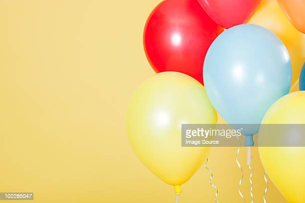 Colourful party balloons against yellow background