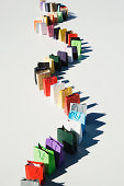 Colourful shopping bags placed in zigzag shape on white platform, elevated view