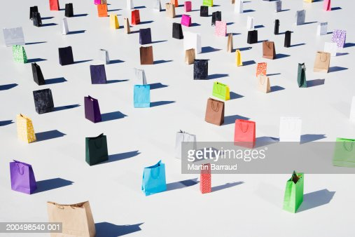 Colourful shopping bags placed on white platform, elevated view
