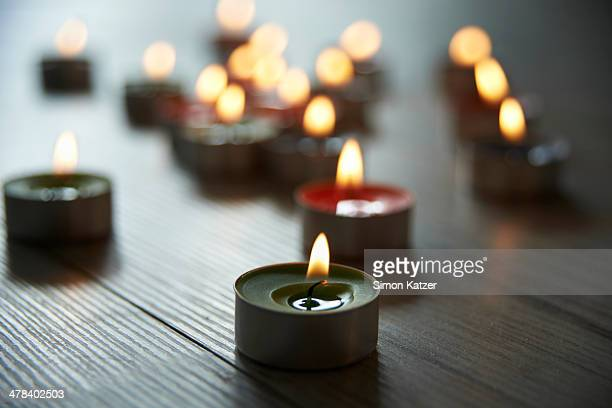 Colourful tea candles burning on wooden floor