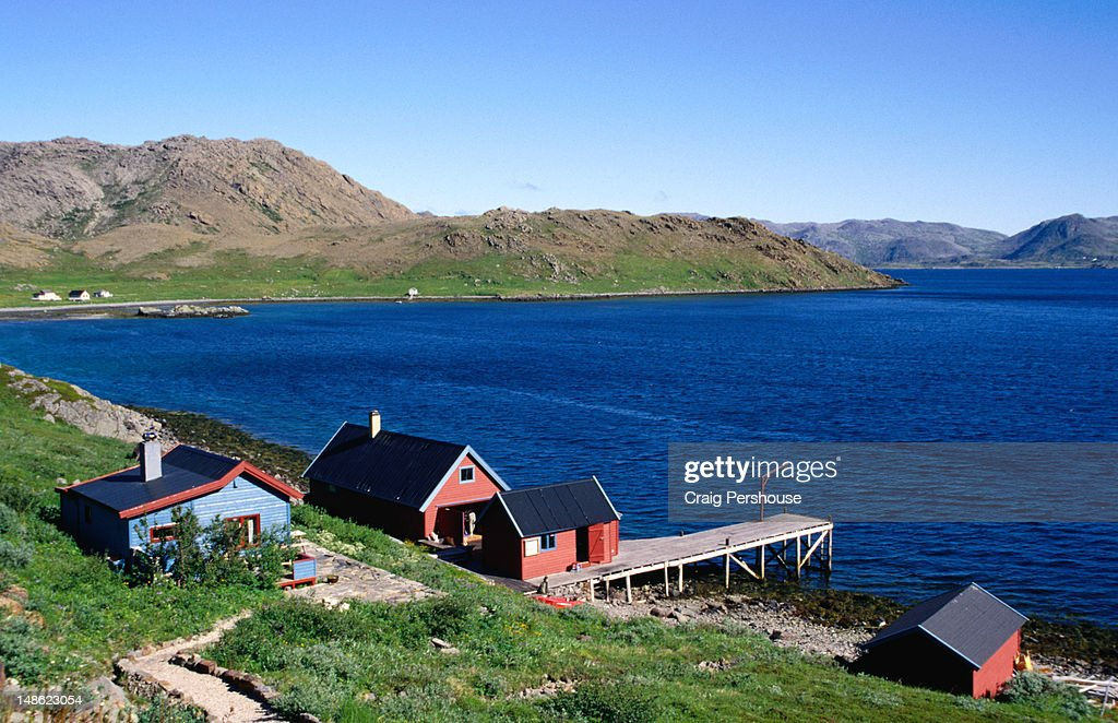 Colourful timber houses and a wharf by the deep blue waters of Skipsfjorden in the far north, Coastal Finnmark.