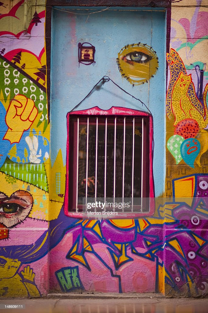 Colourful wall paintings with eyes, and lips around a window with bars. : Stock Photo