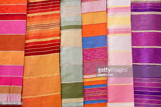 Colourful woven textiles on market stall (full frame)