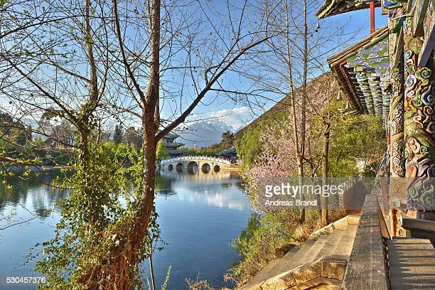 Colourful Yunnan wood carvings with Suocui Bridge and Moon Embracing Pavilion, Lijiang, Yunnan, China, Asia