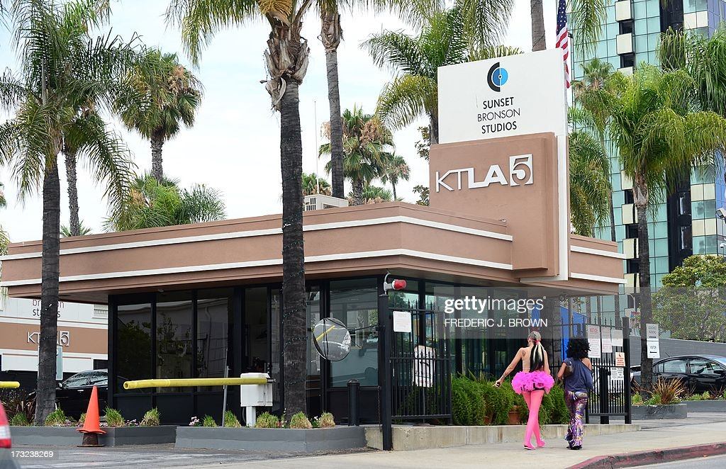 Colourfully dressed pedestrians walk past the offices of televiosn station KTLA in Hollywood, California on July 10, 2013. The Tribune Company, a group which owns 23 television stations including KTLA, announced plans Wednesday to spin off its newspaper division, which includes the Los Angeles Times and Chicago Tribune, separating the struggling unit from its growing television station holdings. Tribune Company last week announced a $2.7 billion deal to buy 19 more local television stations and has said splitting into two distinct companies would give each 'greater financial and operational focus.' AFP PHOTO/Frederic J. BROWN