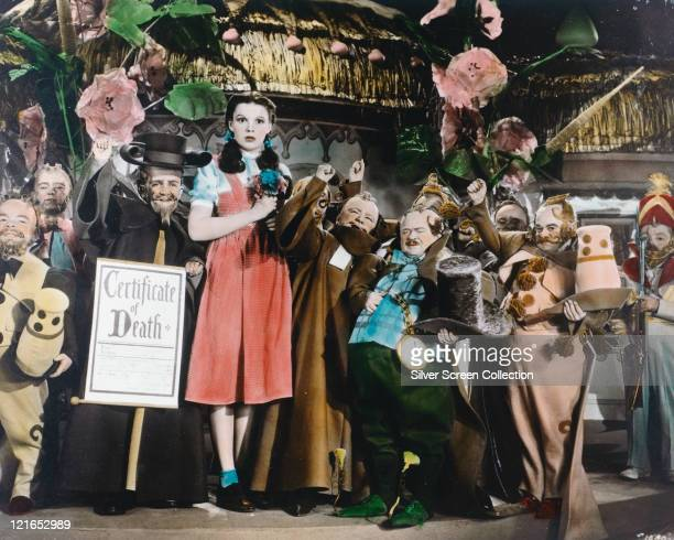 Colourised shot of Judy Garland US actress and singer in costume and surrounded by a group of munchkins in a publicity still from the film 'The...