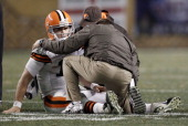 Colt McCoy of the Cleveland Browns lays on the ground while speaking to athletic trainers after a helmet to helmet hit from James Harrison of the...