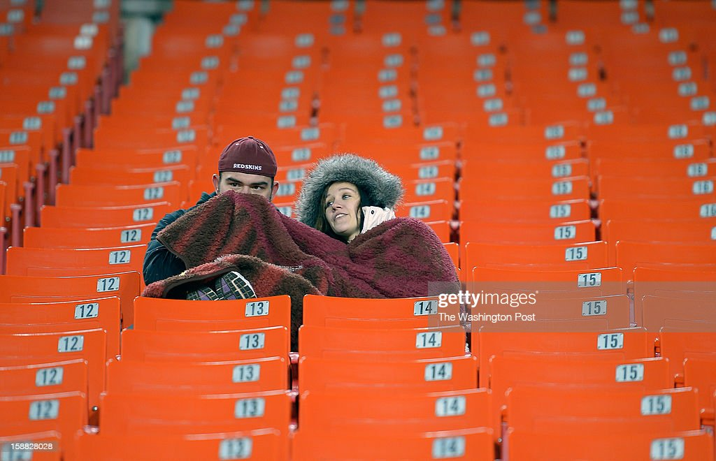 Coltan Strong, left, and Kaleigh Downing , both of Virginia Beach VA, bundle up in the stands 3 1/2 hours before the Washington Redskins play the Dallas Cowboys for first place of the NFC East division and a playoff spot at FedEx in Landover MD, December 30, 2012 .