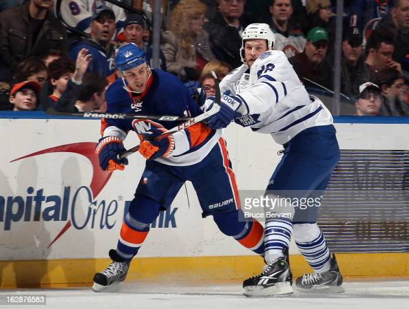 Colton Orr of the Toronto Maple Leafs hits Marty Reasoner of the New York Islanders at the Nassau Veterans Memorial Coliseum on February 28 2013 in...