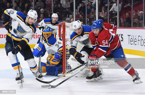 Colton Parayko and Brayden Schenn of the St Louis Blues defends against Charles Hudon of the Montreal Canadiens in the NHL game at the Bell Centre on...