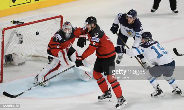Colton Parayko of Canada check the puck over Calvin Pickard and VelliMatti Savinainen of Finland during the 2017 IIHF Ice Hockey World Championship...
