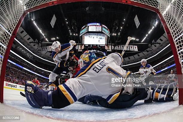 Colton Parayko of the St Louis Blues and Marcus Kruger of the Chicago Blackhawks chase the puck in front of goalie Brian Elliott during Game Four of...