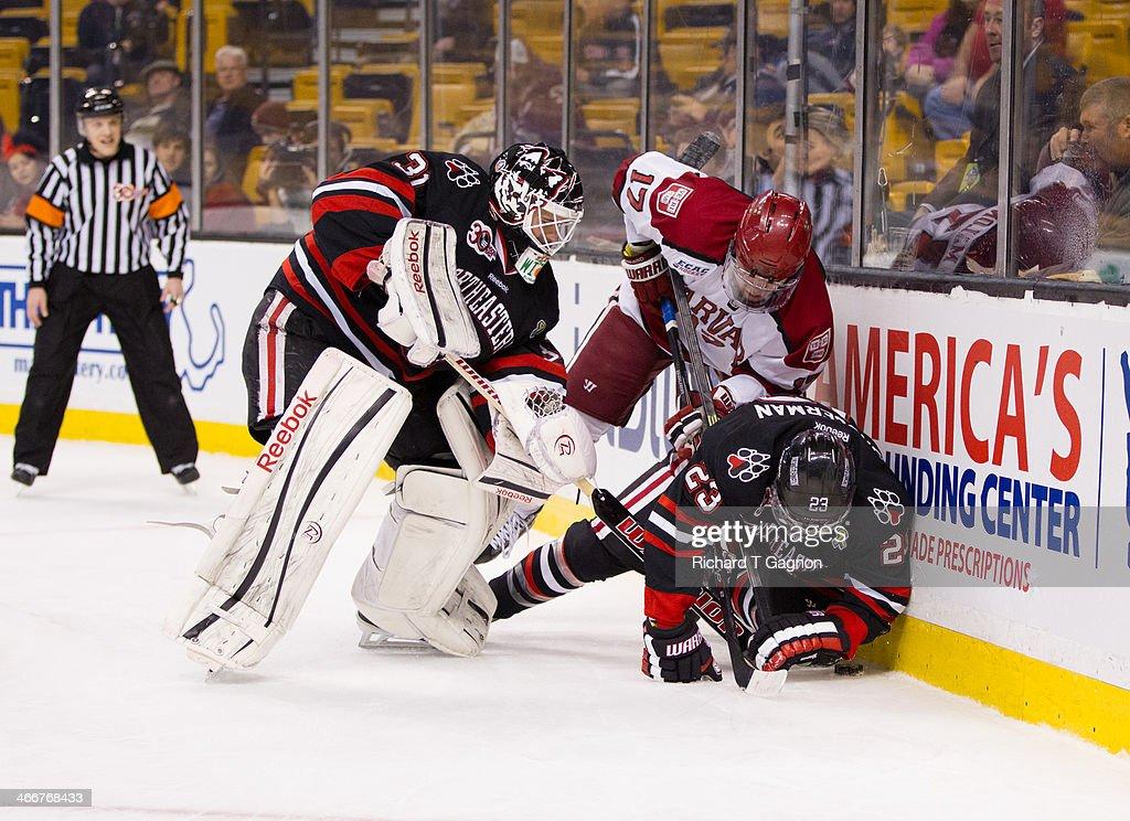 Colton Saucerman and Clay Witt the Northeastern University Huskies battle Sean Malone of the Harvard Crimson behind the net during NCAA hockey action...