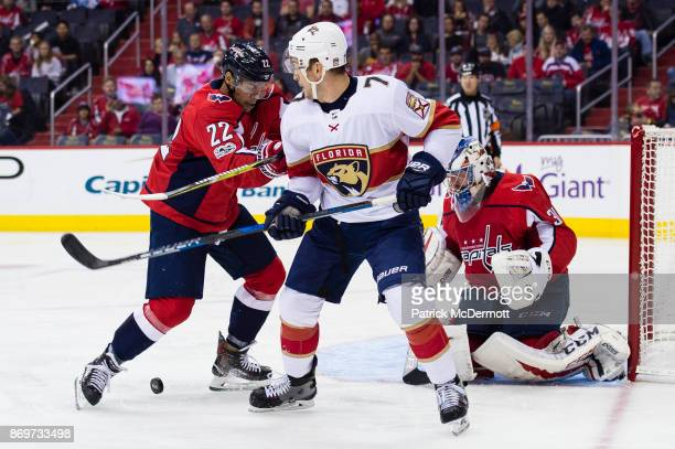 Colton Sceviour of the Florida Panthers and Madison Bowey of the Washington Capitals battle for the puck in front of Philipp Grubauer in the second...