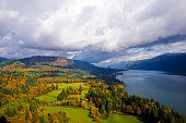 Panorama of Columbia River Gorge Cape Lookout point of view landscaping floodplain with green meadows, autumn trees, lit by the rays of the sun and cloudy sky and the river, leaving the horizon.