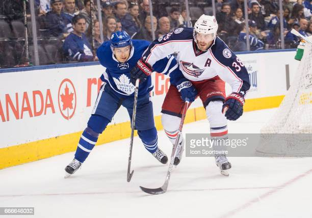 Columbus Blue Jackets center Boone Jenner battles with Toronto Maple Leafs defenseman Connor Carrick during the third period in a game on April 9 at...